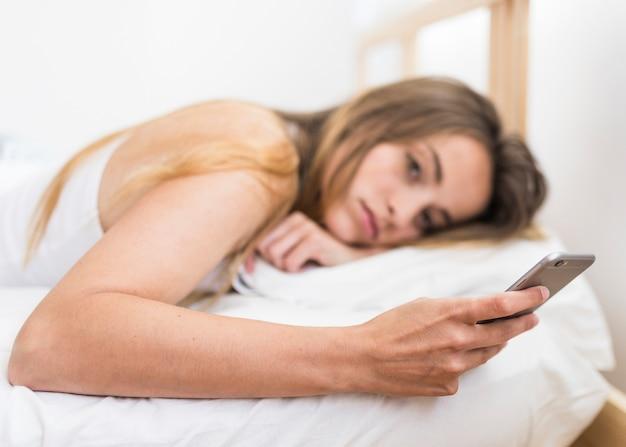 Jeune femme, coucher lit, utilisation, téléphone portable Photo gratuit