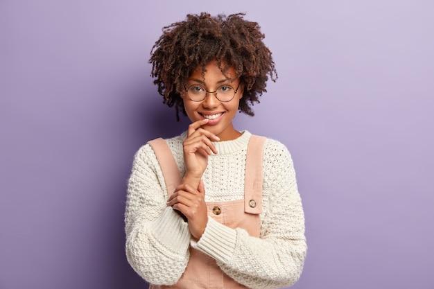 Jeune Femme Avec Coupe De Cheveux Afro Portant Pull Blanc Et Salopette Rose Photo gratuit