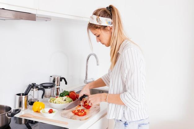 Jeune femme coupe le poivron avec un couteau sur le comptoir de la cuisine Photo gratuit