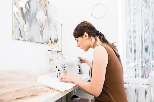 Jeune femme cousant sur une machine à coudre Photo gratuit