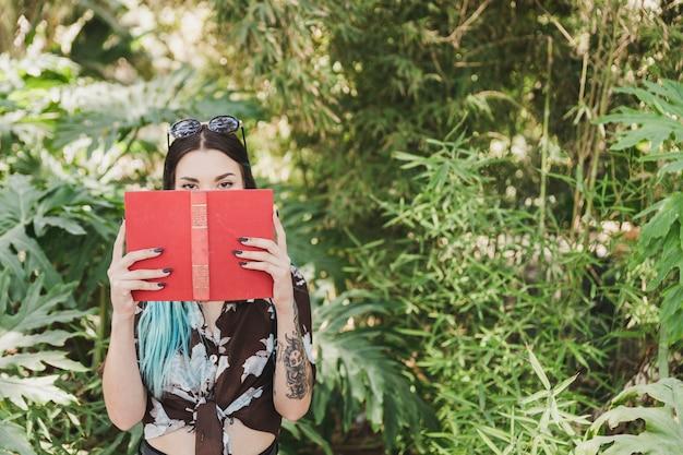 Jeune femme, couverture, bouche, livre, debout, devant, croissant, usines Photo gratuit