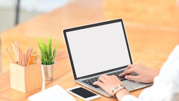 Jeune Femme Créative Surfer Sur Internet En Utilisant Un Ordinateur Portable à écran Blanc Blanc Tout En étant Assis Au Bureau En Bois Moderne. Photo Premium