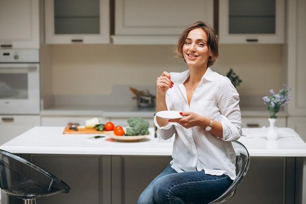 Jeune femme, cuisine, boire café, matin Photo gratuit