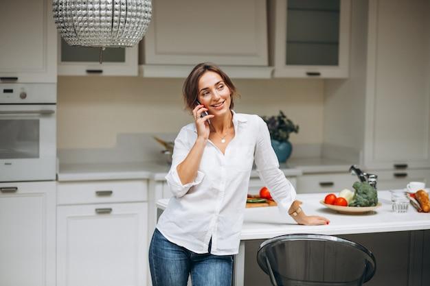 Jeune femme, cuisine, cuisine, petit déjeuner, conversation, téléphone Photo gratuit