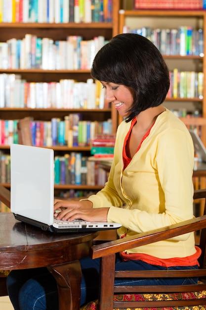 Jeune femme dans une bibliothèque, écrit sur ordinateur portable d'apprentissage Photo Premium
