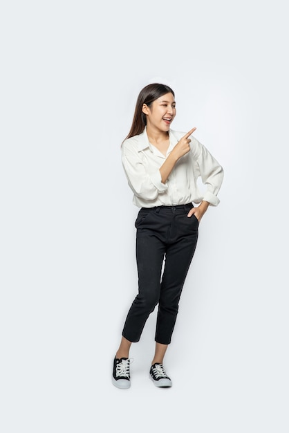 Une Jeune Femme Dans Une Chemise Blanche Et Pointant Vers Le Haut Photo gratuit