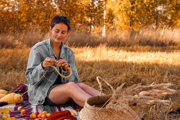 Une jeune femme dans un élégant vêtement tricotant un chapeau jaune avec une aiguille et de la laine naturelle, assise sur un plaid avec un panier de pique-nique et des pommes. concept d'un travail indépendant en plein air Photo Premium