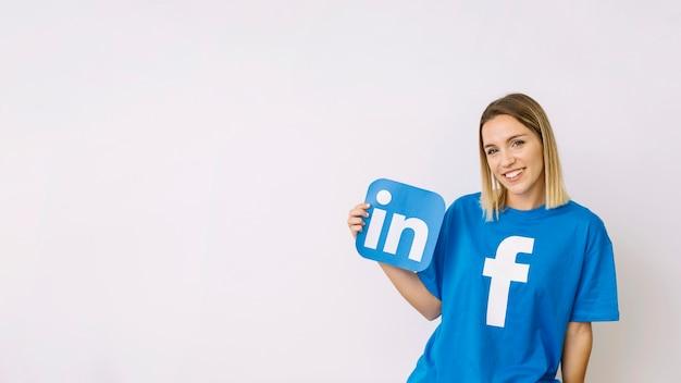 Jeune femme dans facebook t-shirt tenant icône de linkedin Photo gratuit