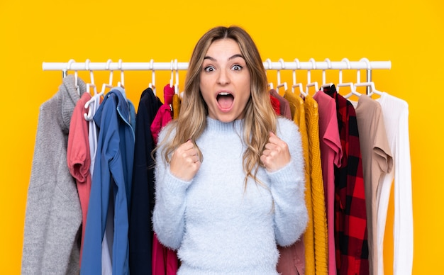 Jeune Femme Dans Un Magasin De Vêtements Sur Un Mur Jaune Isolé Célébrant Une Victoire Photo Premium