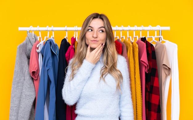 Jeune Femme Dans Un Magasin De Vêtements Sur Un Mur Jaune Isolé En Pensant à Une Idée Photo Premium