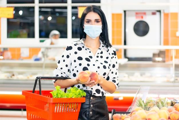 Jeune Femme Dans Un Masque Médical Jetable Fait Ses Courses Au Supermarché Photo Premium