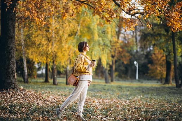 Jeune femme dans un parc en automne, boire du café Photo gratuit