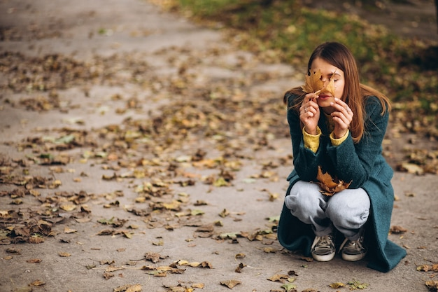 Jeune Femme Dans Le Parc, Fermant Les Yeux Avec Des Feuilles D'automne Photo gratuit