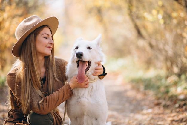 Jeune femme dans un parc avec son chien blanc Photo gratuit