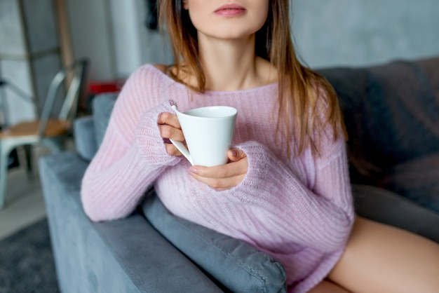 Une Jeune Femme Dans Un Pull Rose Garde La Tasse De Café, Close-up Photo Premium