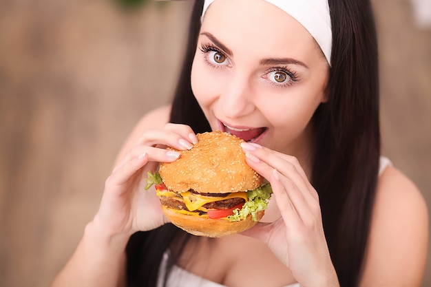 Jeune femme dans un restaurant gastronomique mange un hamburger, elle se comporte mal Photo Premium