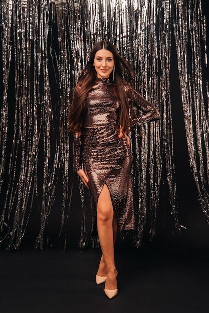 Jeune Femme Dans Une Robe Brillante Sur Rideau De Guirlandes D'argent Photo Premium