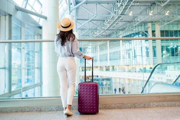 Jeune femme dans un salon d'aéroport en attente d'un avion. Photo Premium