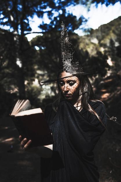 Jeune femme, dans, sorcier, costume, lecture, livre, dans, forêt Photo gratuit