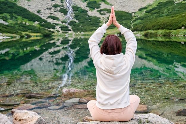 Jeune Femme Dans Un Sweat à Capuche Blanc Pratiquant Le Yoga Sur Une Rive Du Lac Avec De L'eau Transparente Avec Une Vue Imprenable Sur La Cascade. Méditation Et Loisirs Dans La Nature Entre Les Montagnes Photo Premium
