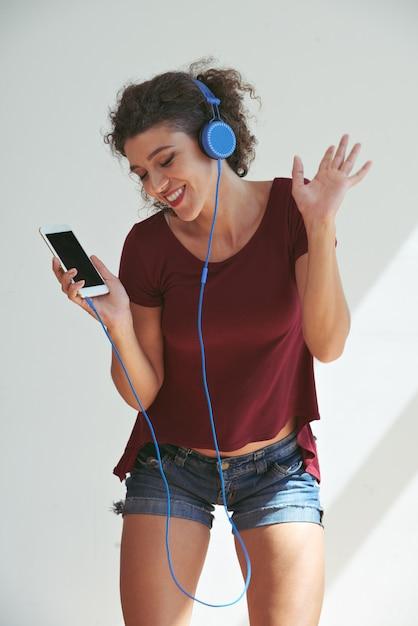 Jeune femme danse sur ses chansons préférées avec des écouteurs Photo gratuit