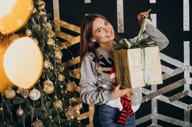 Jeune femme déballant le cadeau de noël près du sapin de noël Photo gratuit