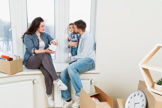 Jeune femme déballant les cartons en regardant son mari aimant son fils Photo gratuit
