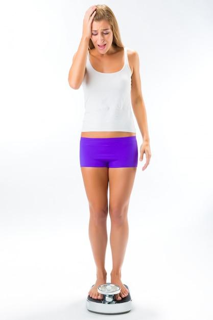 Jeune femme debout sur une balance Photo Premium