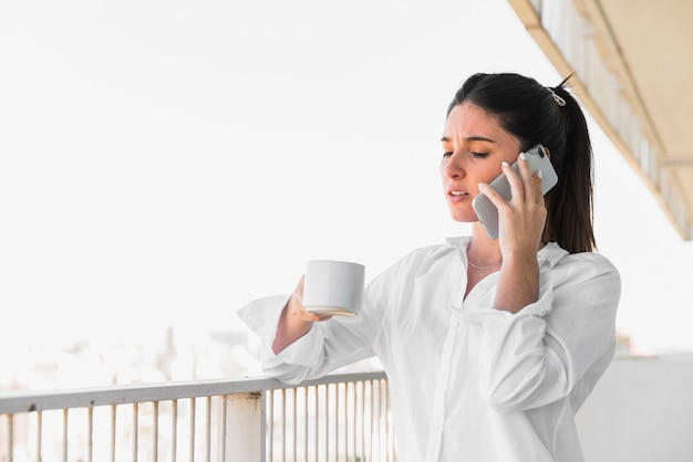 Jeune femme, debout, balcon, tenue, tasse café, parler, sur, téléphone portable Photo gratuit