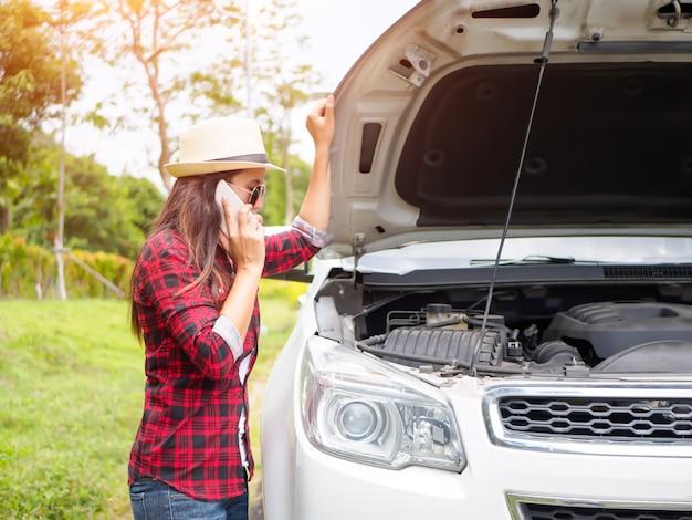 Jeune femme debout sur le bord de la route avec une voiture cassée. Photo Premium