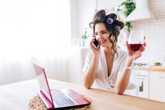 Jeune Femme Debout Dans La Cuisine Et Parler Au Téléphone. Tenant Un Verre De Vin Rouge à La Main. Femme De Ménage Avec Des Bigoudis Dans Les Cheveux. Ménagère Insouciante. Photo Premium