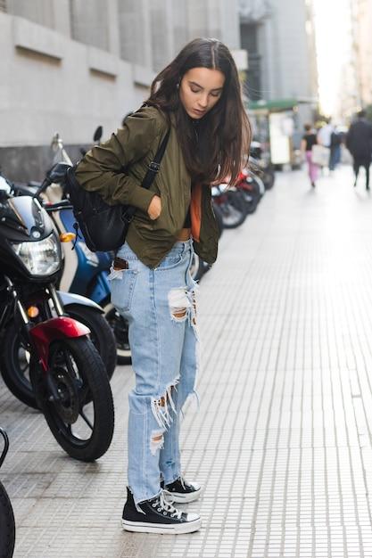 Jeune femme debout dans la rue avec un sac à dos sur l'épaule en regardant quelque chose dans la poche de la veste Photo gratuit