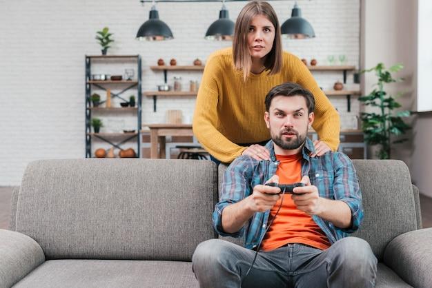 Jeune femme debout derrière son mari assis sur un canapé jouant au jeu vidéo Photo gratuit