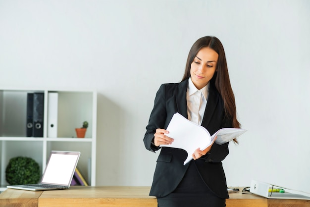 Jeune femme debout devant un bureau, lisant des documents Photo gratuit