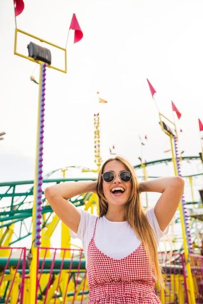 Jeune femme, debout, devant, montagnes russes, rire Photo gratuit