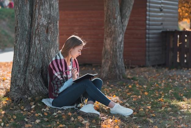 Jeune femme debout près d'un arbre long shot Photo gratuit
