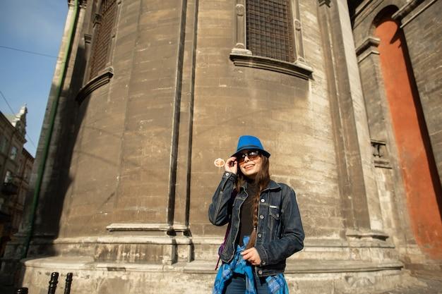 Jeune femme debout près de l'église dans la vieille ville de lviv. ukraine Photo Premium