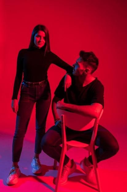 Jeune femme debout près d'un homme sur une chaise Photo gratuit