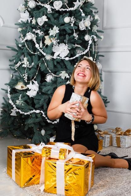 Jeune Femme Défaisant Le Ruban Sur Les Cadeaux De Noël. Photo Premium