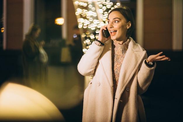 Jeune femme en dehors de la rue de nuit avec des lumières Photo gratuit