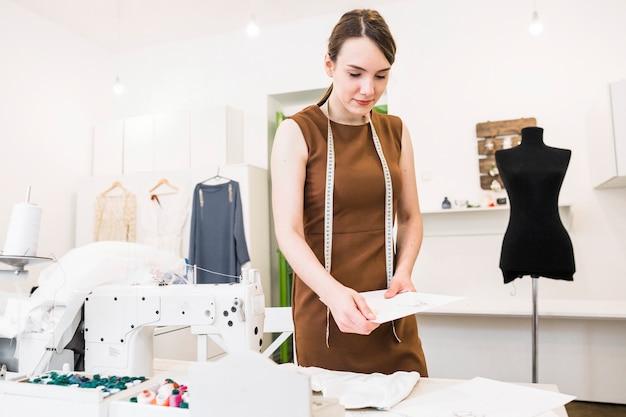Jeune femme designer tenant des croquis de mode dans le magasin Photo gratuit