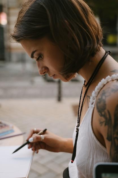 Jeune Femme Dessine Au Carnet De Croquis Avec Un Crayon à L'extérieur Dans La Rue Photo gratuit
