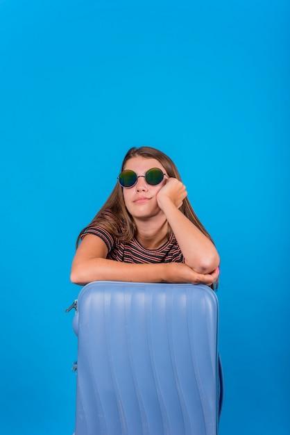 Jeune femme disparue et s'appuyant sur la valise Photo gratuit