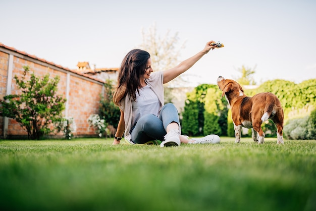 Jeune femme donnant une friandise à son chien dans le jardin. Photo Premium