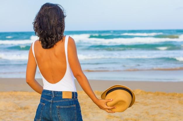 Jeune femme dos à dos sur la plage Photo Premium