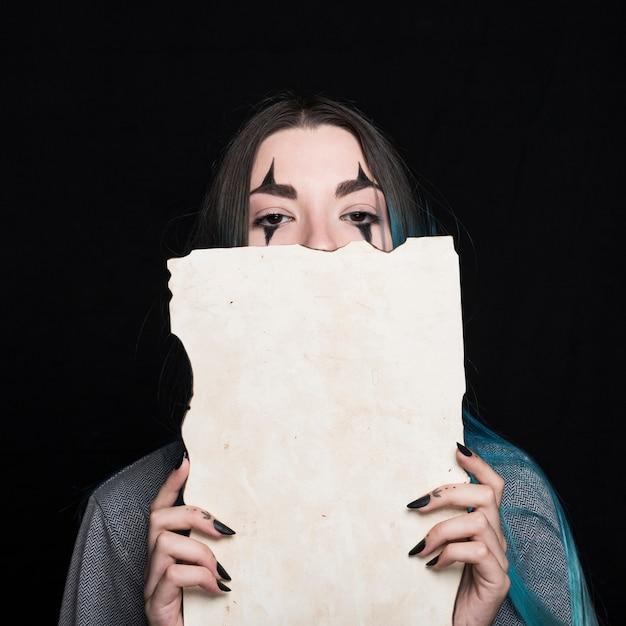 Jeune femme avec du maquillage halloween tenant un morceau de papier Photo gratuit