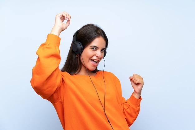Jeune femme écoutant de la musique avec un téléphone portable sur un mur bleu isolé célébrant une victoire Photo Premium