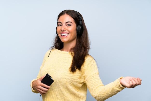 Jeune femme écoutant de la musique avec un téléphone portable sur un mur bleu isolé et dansant Photo Premium