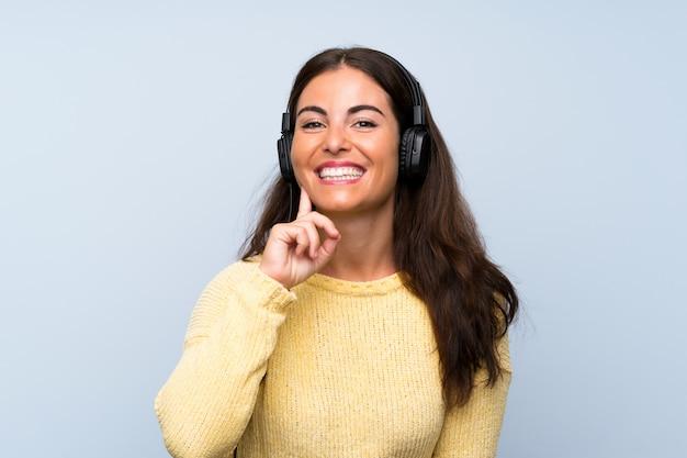 Jeune femme écoutant de la musique avec un téléphone portable sur un mur bleu isolé Photo Premium