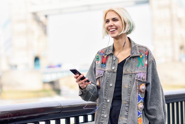Jeune femme écoutant de la musique en ville Photo Premium